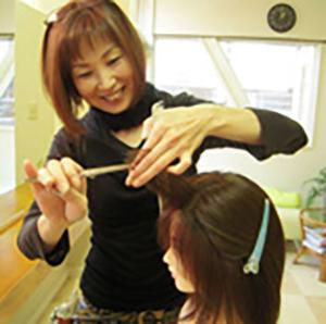 カットしている美容師の菅谷