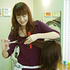 カットしている美容師の山崎